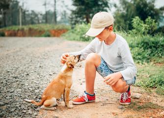 Wall Mural - Boy met a little homeless puppy on the street