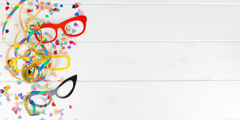 carnival party background with confetti, streamer and glasses
