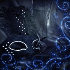 Image of elegant dramatic black venetian mask over tulle background.