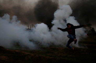 Palestinian demonstrator runs from tear gas fired by Israeli troops during clashes, near the border with Israel in the east of Gaza City
