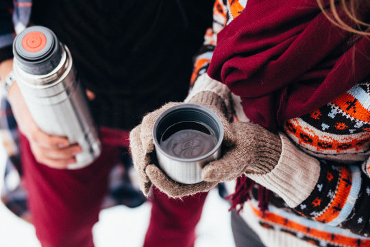 woman hands pours hot tea or coffee out of thermos on winter forest background. girl using a thermos in on a snowy day. metallic cup