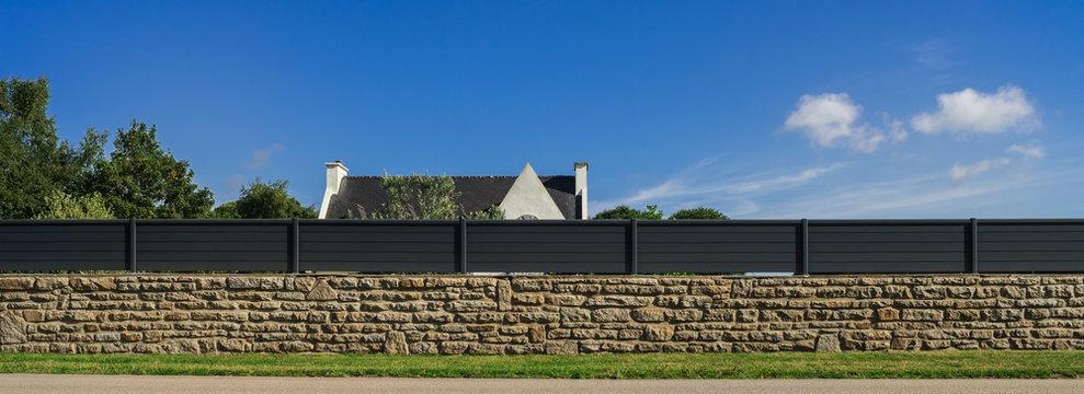 Moderner Gartenzaun aus lackiertem Aluminium auf Natursteinmauer als Panorama - Modern garden fence made of varnished aluminium on natural stone wall as panorama