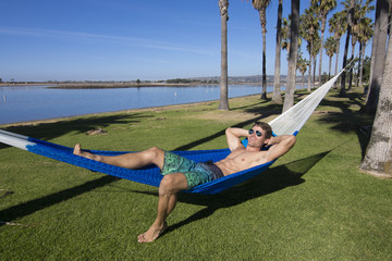 Sexy beach guy tanning in a hammock