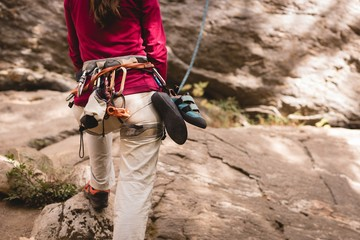 Female hiker preparing herself to climb the rocky mountain