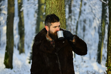 Man in fur coat drinks from metal cup.