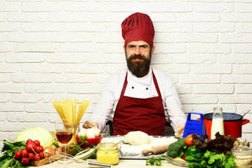 Man with beard by kneaded dough on white brick background