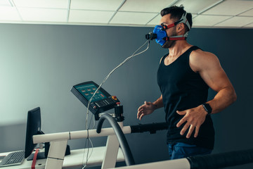 Fitness man running on treadmill testing his performance