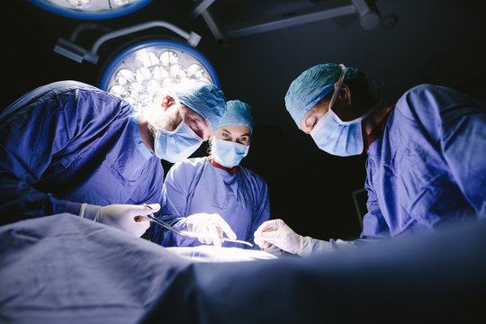 Group of surgeons doing surgery in hospital
