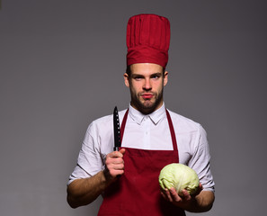 Man with beard holds cabbage and knife on grey background.