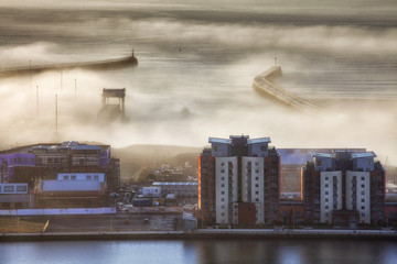 Editorial SWANSEA, UK - JANUARY 10, 2018: A heavy fog engulfs the west and east piers and the entrance to the docks at Swansea city UK on a Winter morning.