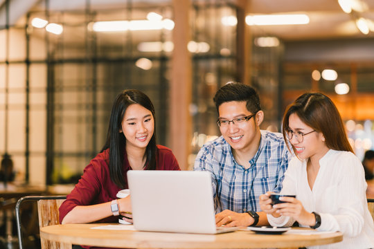 Young Asian college students group or coworkers using laptop computer together at cafe or university. Casual business, freelance work, coffee break meeting, e-learning or e-commerce activity concept