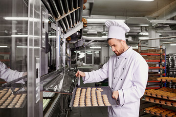 A man baker with a tray of cupcakes in a bakery.