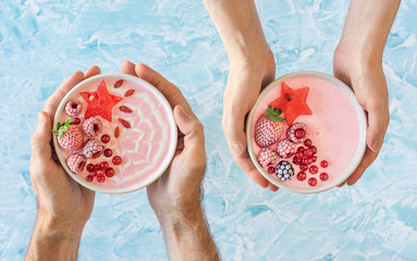 Male and Female Hands Holding Pink Berry Yogurt Smoothie Bowls Topped with Chilled and Fresh Fruit