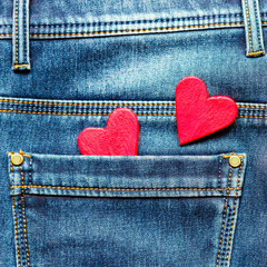 two hearts on a background of a jeans pocket close-up.Valentines Day background consept.