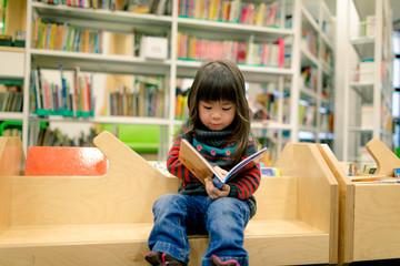 little girl reading a book in a library