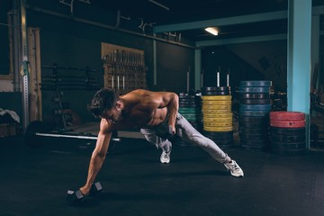 Muscular man doing push-up with dumbbells