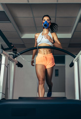 Runner with mask on treadmill in sports science laboratory