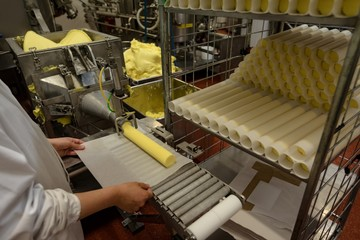 Worker wrapping food rolls in the paper