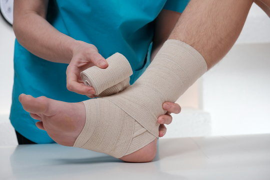 Close-up of male doctor bandaging foot of female patient