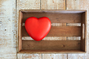 Red heart in a wooden box on the table. Concept Valentine's Day.