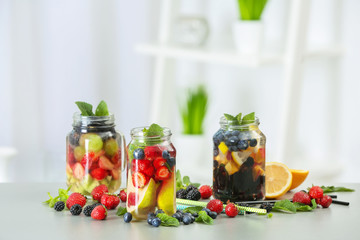 Mason jars of infused water with fruits and berries on table
