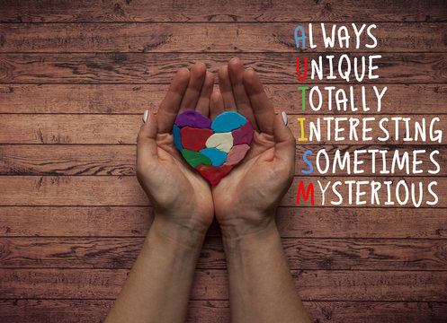 World autism awareness day. Lady's hands holding a multicolored heart as symbol of autism awareness day.