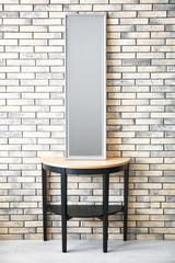 Modern mirror on stand near brick wall