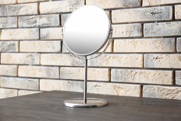 Modern mirror on wooden table near brick wall