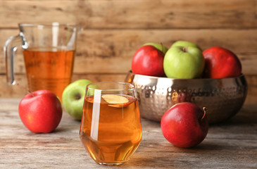 Glass of delicious apple juice on table