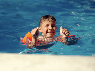 Caucasian boy swimming in the pool and holding thumb up.