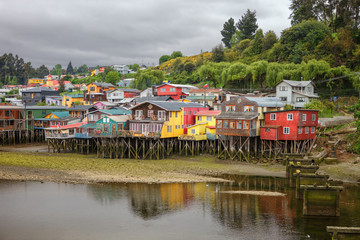Traditional wooden houses built on stilts (palafitos) along the waters edge in Castro, Chiloe, Chile