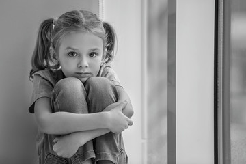 Sad little girl sitting on windowsill, black and white effect