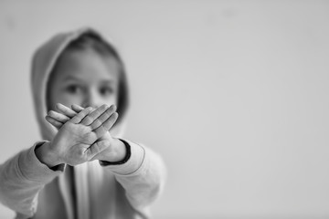 Sad little girl making stop gesture on grey background, black and white effect