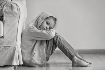 Sad little girl sitting on floor indoors, black and white effect