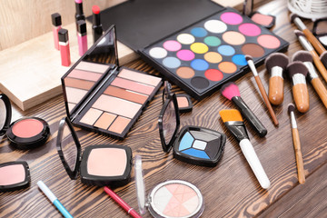 Decorative cosmetics and tools of professional makeup artist on dressing table