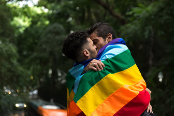 Gay Couple Kissing with Rainbow Flag in the Park