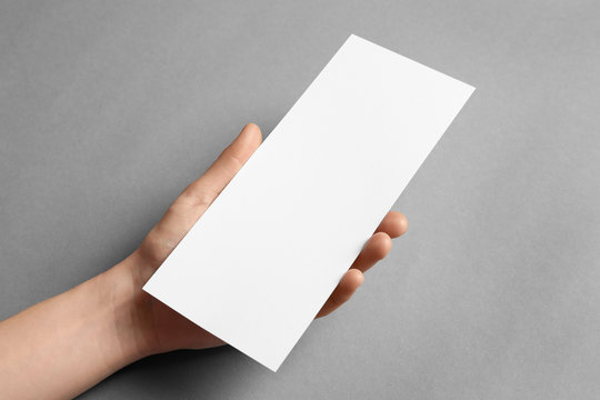Woman holding blank card on grey background. Mock up for design