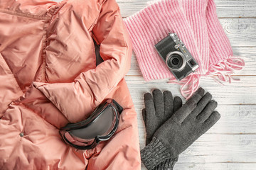 Warm clothes with photo camera and ski goggles on wooden background. Winter vacation concept