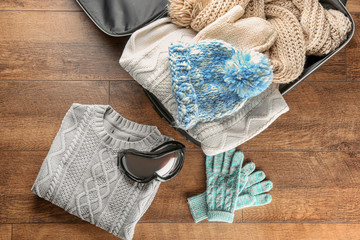 Open suitcase with warm clothes and ski goggles on wooden floor. Winter vacation concept