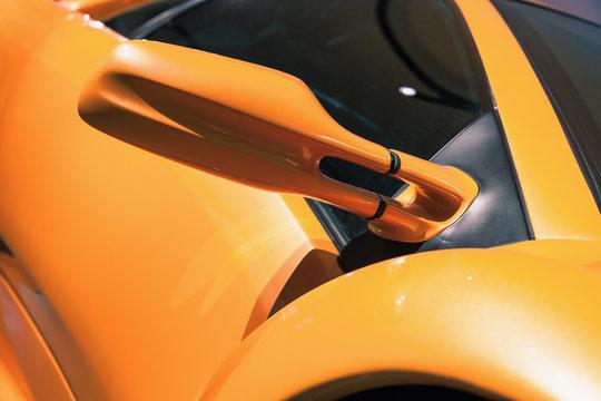 Luxury yellow sports car mirror, close up