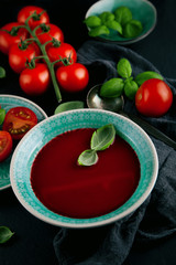 Fresh Tomato soup in a bowl with tomatoes and basil on a slate kitchen table