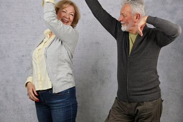 Happy stylish elderly couple dancing and laughing