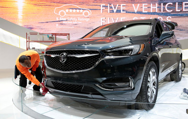 A worker details a 2018 Buick Avenir SUV on the display floor before the start of Press Days for the North American International Auto Show at Cobo Center in Detroit,
