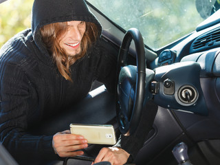 Burglar thief breaking into car stealing smartphone