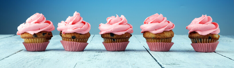 Tasty cupcakes on wooden background. Birthday cupcake in pink color