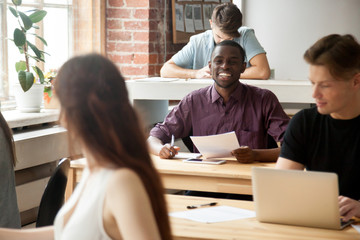 Cheerful african-american new employee talking to female colleague in multi-ethnic co-working space, friendly smiling man holding documents asking question woman coworker, help teamwork in office