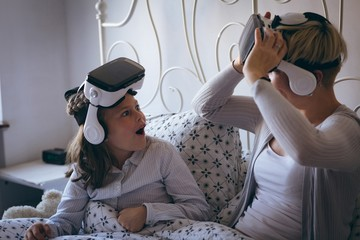 Mother and daughter using virtual reality headset on bed