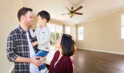 Young Mixed Race Caucasian and Chinese Family Inside Empty Room with Wood Floors.