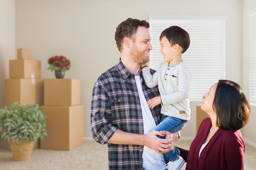 Young Mixed Race Caucasian and Chinese Family Inside Empty Room with Moving Boxes.