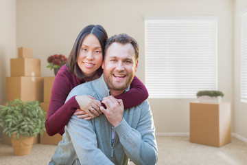 Mixed Race Caucasian and Chinese Couple Inside Empty Room with Moving Boxes.